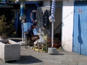 San Remo. Ein Fischer, der seine Netze flickt. Urlaub an der italienischen Riviera in Ligurien